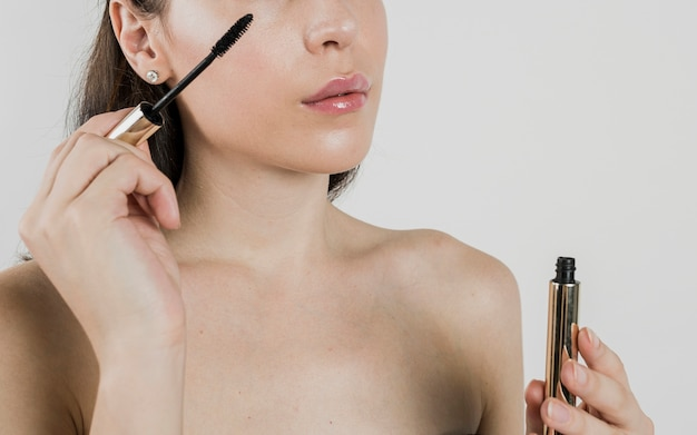 Vrouw die mascara in studio toepast