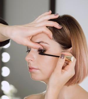 Vrouw die mascara op mooi model toepast