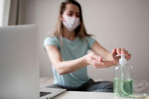 Vrouw die masker binnen draagt en handdesinfecterend middel gebruikt