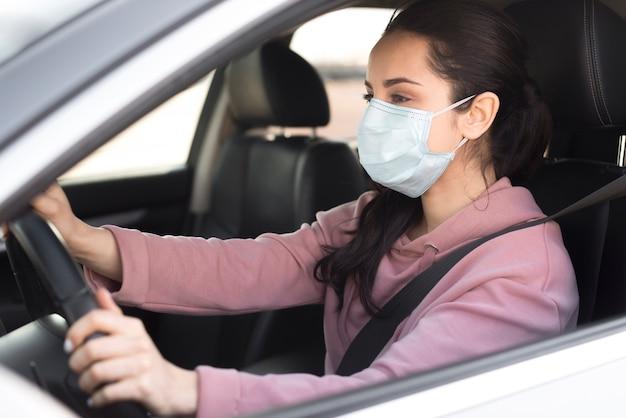 Vrouw die masker binnen haar eigen auto zijaanzicht draagt