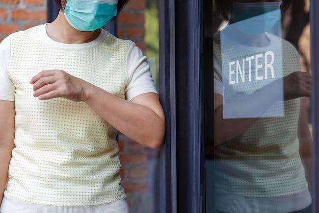 Vrouw die masker draagt dat de deur met de elleboog opent voor beschermingsbesmetting covid-19