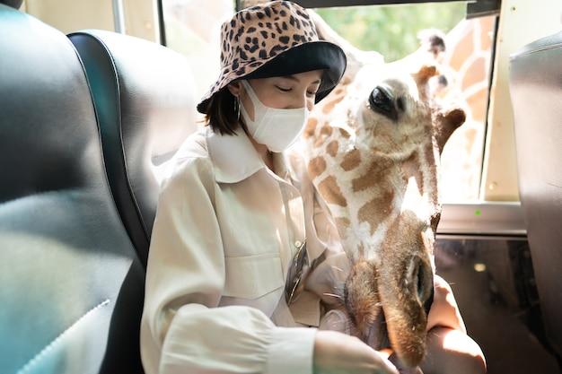 Vrouw die masker met giraf draagt die op voedsel van busvenster in dierentuin wacht
