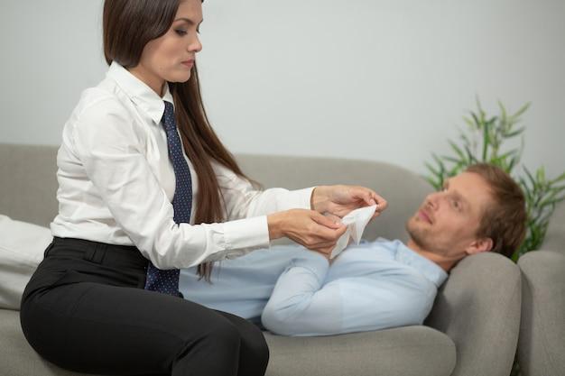 Vrouw die masker op het gezicht van haar echtgenoot zet. jonge mens die op laag legt en op zijn vriendin wacht om gezichtsmasker op hem te zetten. focus op vrouwelijke handen. spa-behandelingen concept. mannelijke huidverzorging concept.