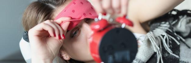 Vrouw die masker uit haar ogen haalt, kijkt naar wekkerpreventie en behandeling van slapeloosheid