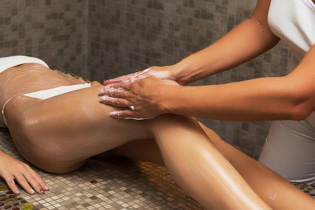 Vrouw die massage met room heeft bij kuuroord