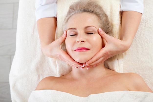 Vrouw die massage voor gezicht en hals krijgt in kuuroordsalon