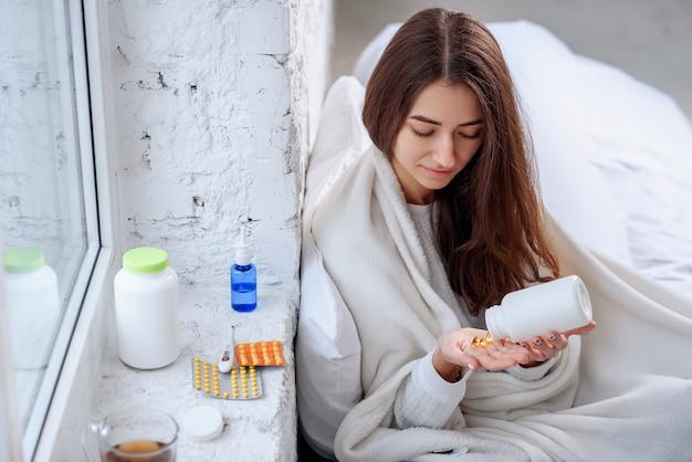 Vrouw die medicijn, tabletten en capsules bij de hand morst