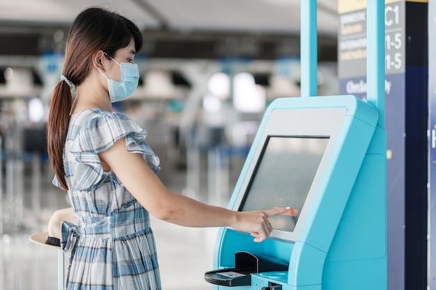 Vrouw die medisch gezichtsmasker draagt en de machine voor zelf inchecken gebruikt op de luchthaventerminal