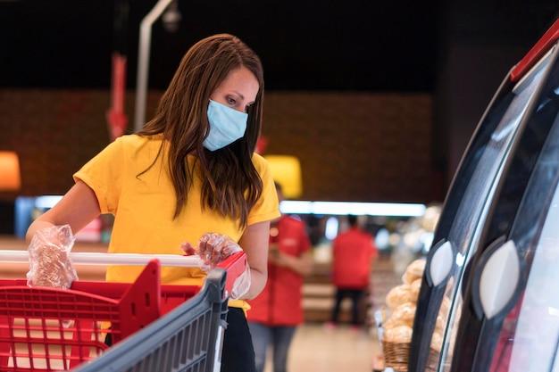 Vrouw die medisch masker draagt bij de winkel
