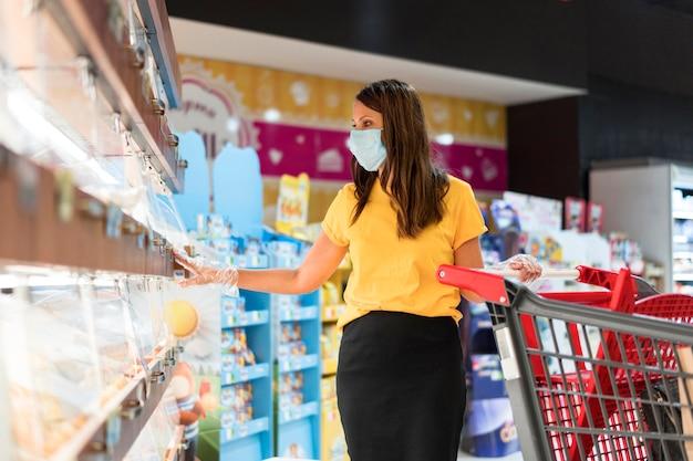 Vrouw die medisch masker draagt dat in de winkel koopt