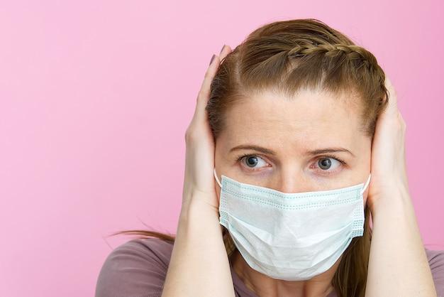 Vrouw die medisch masker draagt dat oren met handen stopt wil niet over virus luisteren.