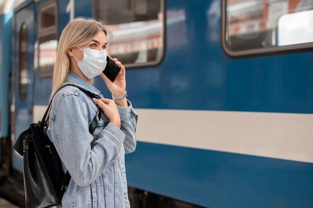 Vrouw die medisch masker draagt en aan de telefoon praat terwijl ze zich klaarmaakt om met de trein te reizen