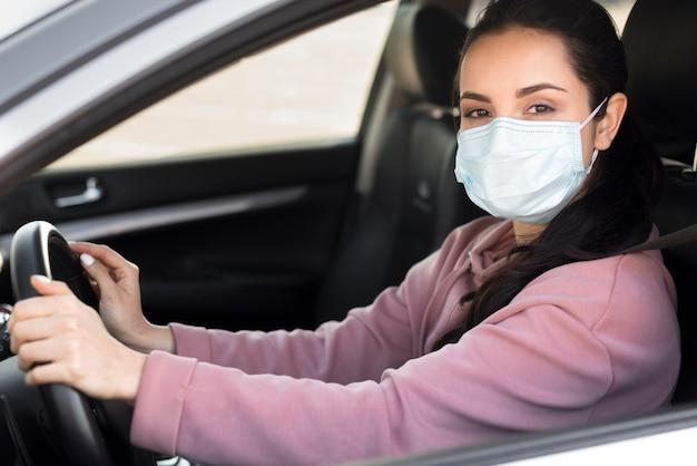 Vrouw die medisch masker in auto draagt