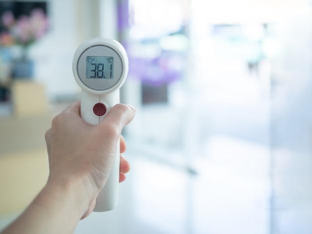 Vrouw die medische infrarood voorhoofdthermometer houdt om lichaamstemperatuur te controleren, die hoge koorts toont. eerste screening om uitbraak van coronavirus te voorkomen. covid-19 en coronavirus concept.