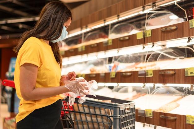 Vrouw die medische masker en handschoenen in een winkel draagt