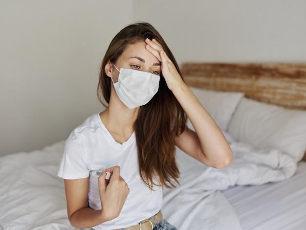Vrouw die medische maskerthermometer draagt die temperatuurhand op voorhoofd controleert