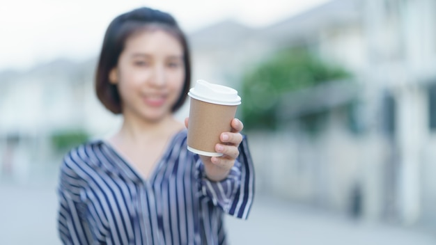 Vrouw die meeneemdocument kop van koffie aan u geeft.