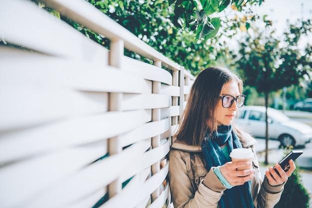 Vrouw die meeneemkoffie houden en slimme telefoon met behulp van