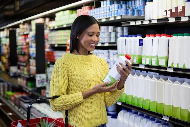 Vrouw die melkfles in zuivelsectie kijken