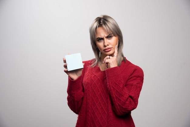 Vrouw die memoblok vasthoudt en aan iets denkt.