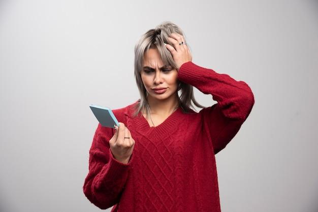Vrouw die memostootkussen op grijze achtergrond bekijkt.