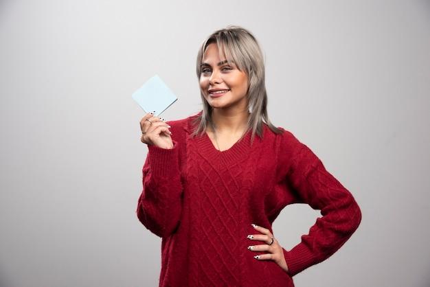 Vrouw die memostootkussen toont en op grijze achtergrond glimlacht.