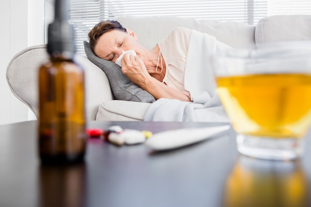 Vrouw die met aftreksel en geneeskunde op voorgrond niest