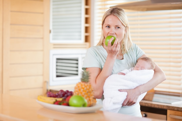 Vrouw die met baby op haar wapens een appel eet