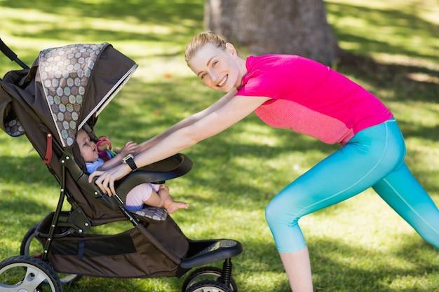 Vrouw die met babywandelwagen uitoefent