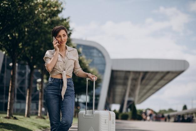 Vrouw die met bagage op de luchthaven reist en aan de telefoon praat