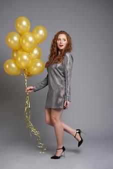 Vrouw die met ballons naar de kant kijkt