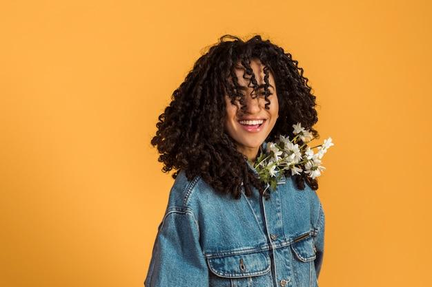 Vrouw die met bloemen onder jasje camera bekijkt