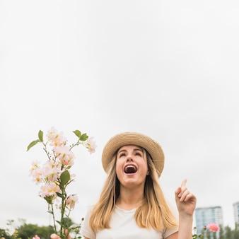 Vrouw die met bloemenboeket vinger benadrukken