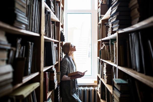 Vrouw die met boek boekenplanken bekijkt
