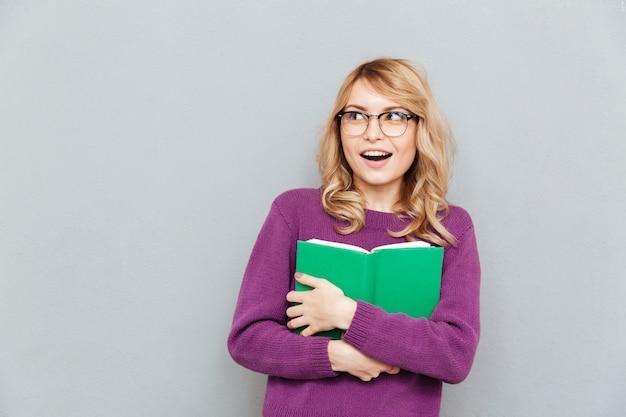 Vrouw die met boek weg kijkt