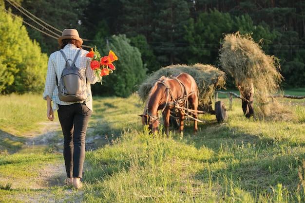 Vrouw die met boeket van rode papavers langs landelijke landweg loopt
