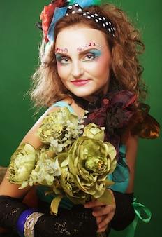 Vrouw die met brigtgezicht grote groene bloemen houdt