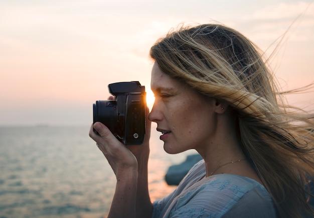 Vrouw die met camera op het strand schieten