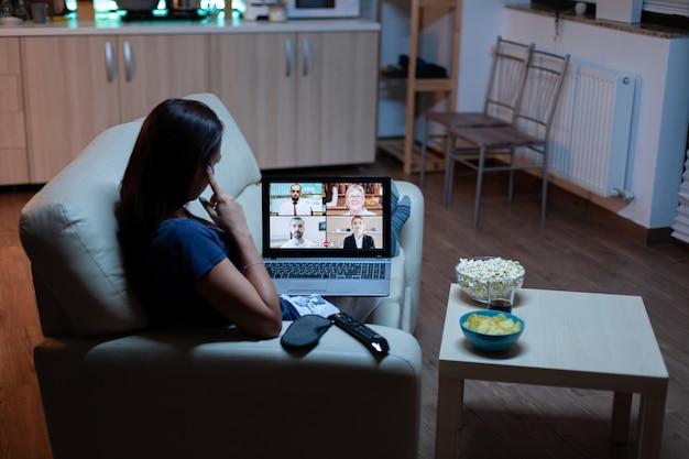 Vrouw die met collega's spreekt op webcam die thuis op bank ligt at