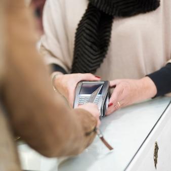 Vrouw die met creditcard door terminal betaalt