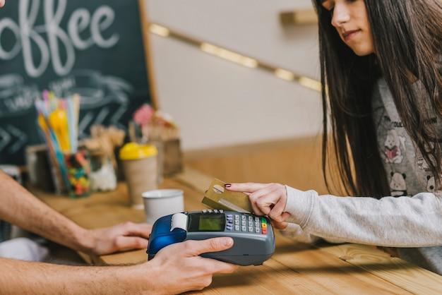 Vrouw die met creditcard in koffie betaalt