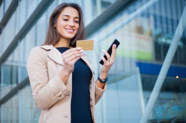 Vrouw die met creditcard winkelt.