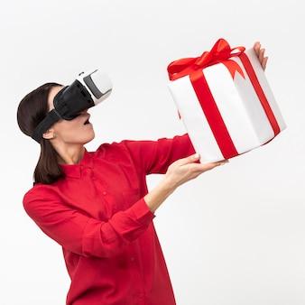 Vrouw die met de doos van de de holdingsgift van de virtuele werkelijkheidshoofdtelefoon