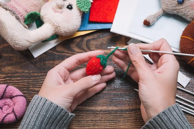 Vrouw die met de hand gemaakt gebreid kerstmisspeelgoed maakt