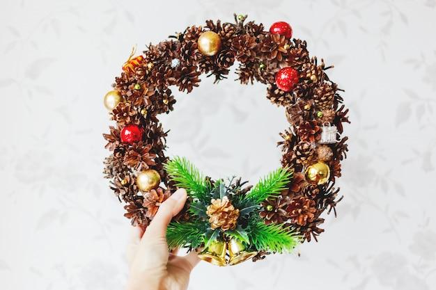 Vrouw die met de hand gemaakte kerstmiskroon houdt. nieuwjaars diy-decoratie gemaakt met dennenappels, glitter, decoratieve ballen en kralen, lijmpistool.