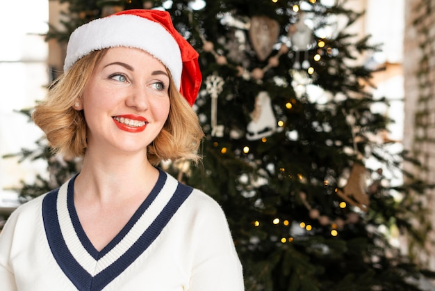 Vrouw die met de hoed van santa weg kijkt