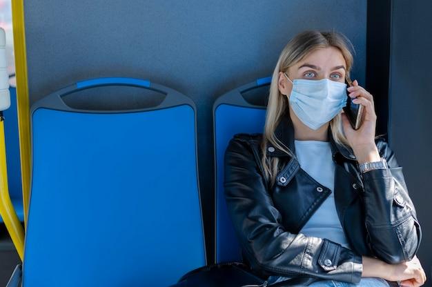 Vrouw die met de openbare bus reist en aan de telefoon praat terwijl ze een medisch masker draagt voor bescherming