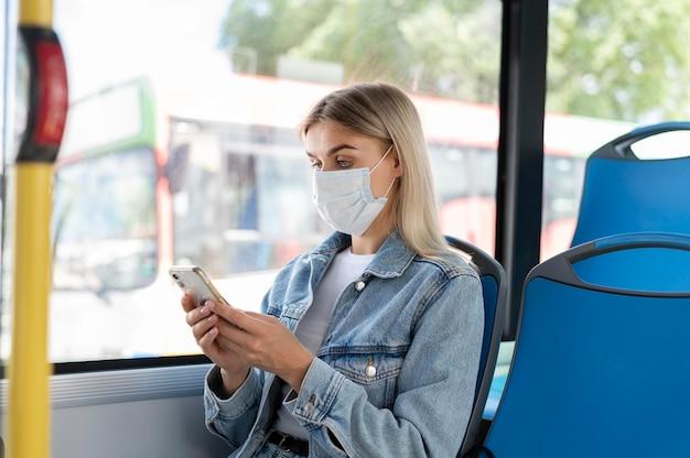 Vrouw die met de openbare bus reist en smartphone gebruikt terwijl ze een medisch masker draagt voor bescherming