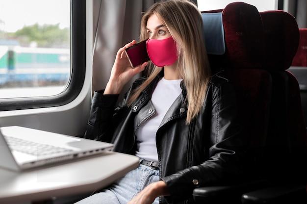 Vrouw die met de trein reist en aan de telefoon praat terwijl ze een medisch masker draagt en op een laptop werkt