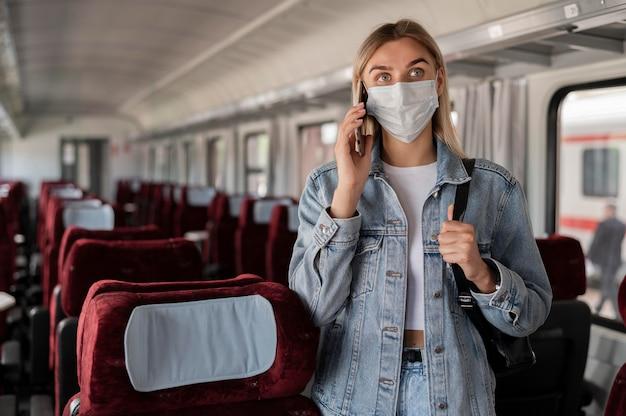 Vrouw die met de trein reist en aan de telefoon praat terwijl ze een medisch masker draagt